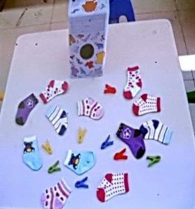 שולחן ועליו גרביים בודדות בכל מיני צבעים וקופסה שבה חור