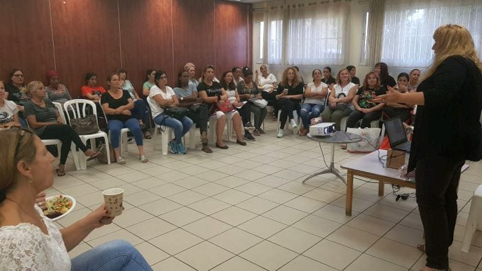 נשים יושבות במעגל בכיתה ומקשיבות למרצה